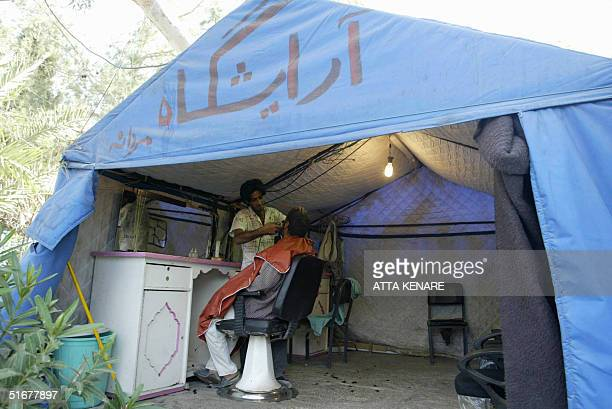 An Iranian barber cuts the hair of a client at a tent 05 November 2004 in the southeastern devastated city of Bam where a powerful earthquake killed...