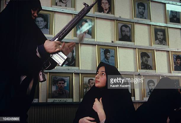 An Iranian Basiji woman teaches schoolgirls to operate automatic assault rifles in a Tehran mosque during the Iran-Iraq War, 1st May 1988. Displayed...