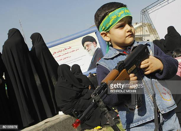 An Iranian boy holds toy gun during a protest in Palestine square in Tehran on March 7 2008 against Israel's military assault on the Gaza Strip with...