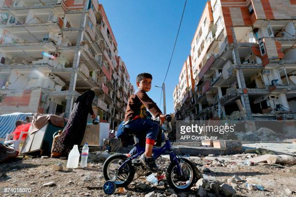 TOPSHOT An Iranian boy rides a bicycle through the rubble past damaged buildings in the town of Sarpole Zahab in Iran's western Kermanshah province...