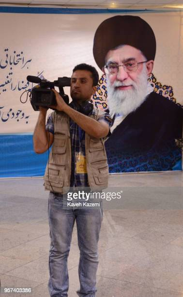 An Iranian cameraman stands in front of a banner with a photo of the supreme leader Ayatollah Ali Khamenei looking on while he shoots candidates...
