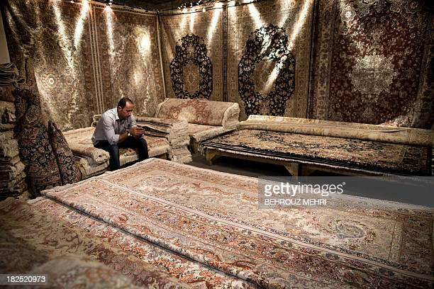 An Iranian carpet businessman sits on his carpets at Iran's international hand-woven carpet exhibition in Tehran on September 29, 2013. Iran exports...