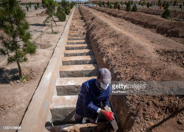 An Iranian cemetery worker covers a dead body of a man who has died from coronavirus disease, with rocks at a grave in the Benhesht-e-Masoumeh...