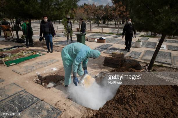 An Iranian cemetery worker in a protective suit sanitizing a pit by lime Before burying a dead body of a man who has died from coronavirus disease ,...