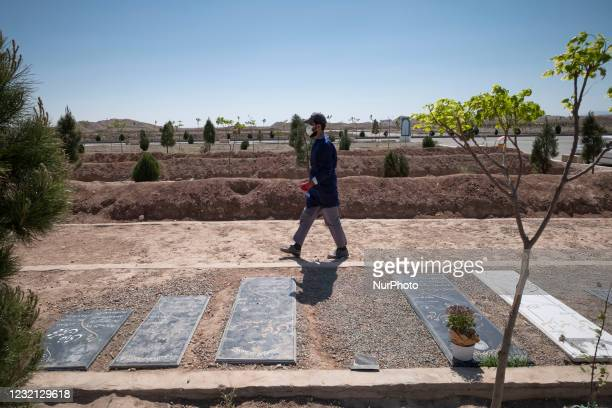 An Iranian cemetery worker wearing a protective suit walks past graves of people who have died from coronavirus disease , in the Benhesht-e-Masoumeh...