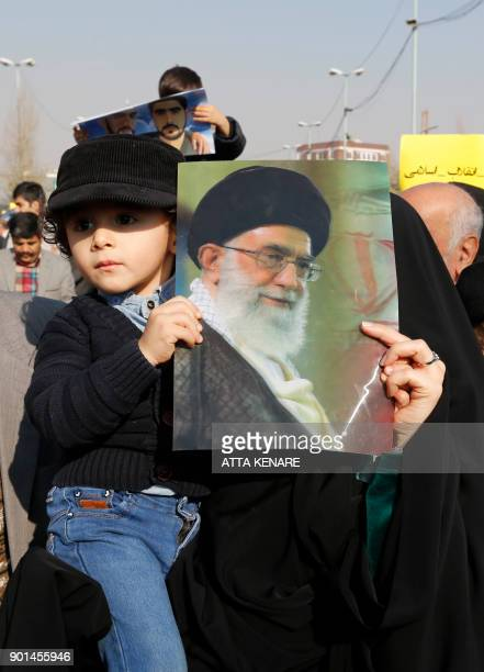 An Iranian child carries a portrait of supreme leader Ayatollah Ali Khamenei during a progovernment march held after the weekly Friday prayers in...