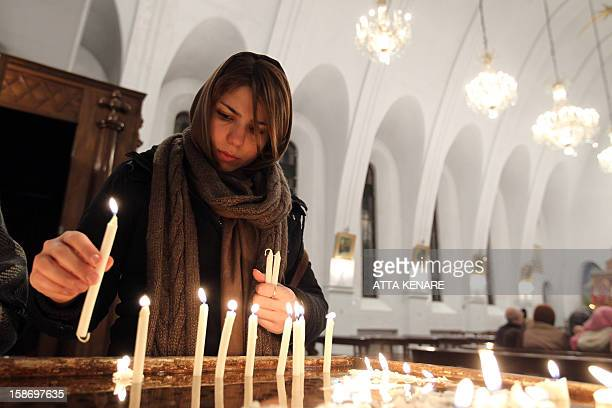 An Iranian Christian woman lights candles during the Christmas Eve mass at the St Gregor Armenian Catholic church in Tehran on December 24 as...