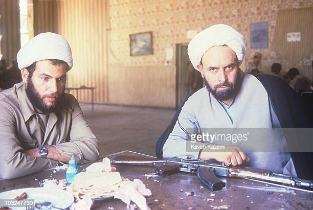 An Iranian clergyman armed with an AK47 automatic assault rifle sits at table in Hajomran Iraq with a younger man in a turban after an Iranian...