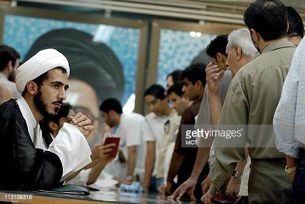 TEHRAN IRAN An Iranian Clergyman serving as an investigator keeps his hands crossed ashe watches voters cast their ballots at a mosque in Tehran that...