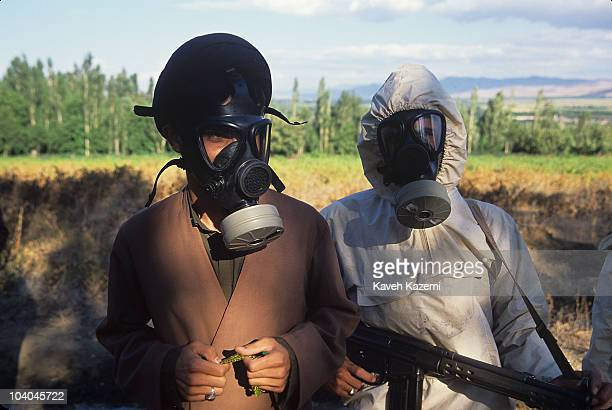 An Iranian clergyman wearing a turban and gas mask , stands next to a member of the Basiji in a chemical warfare suit, at the site of a chemical...