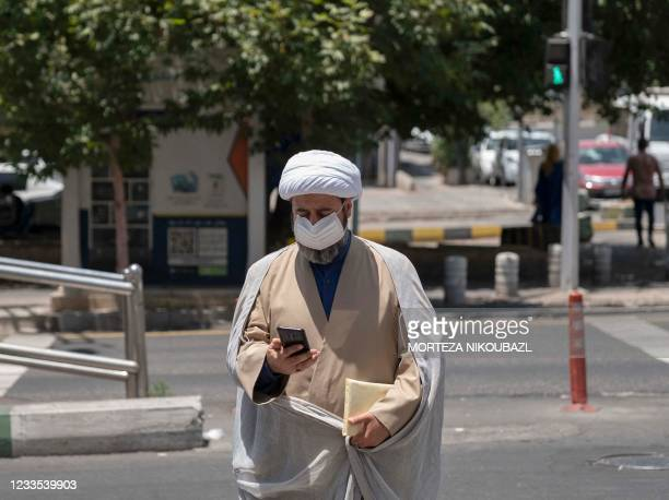 An Iranian cleric looks at his smartphone as he crosses an avenue in northern Tehran on June 19, 2021. - Ultraconservative cleric Ebrahim Raisi was...
