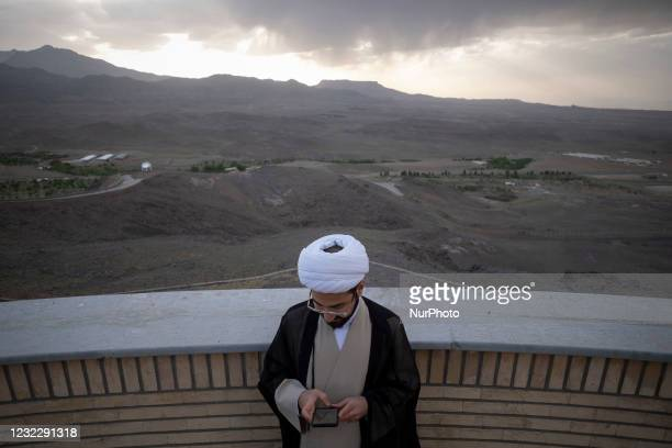 An Iranian cleric uses an application on his smartphone to find the new moon of Muslims holy month of Ramadan while standing in the Imam Ali...