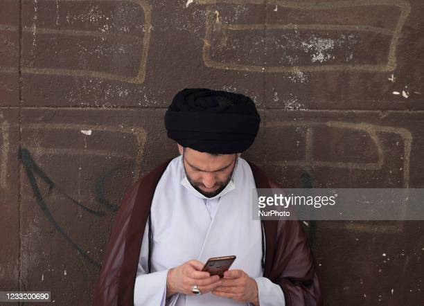 An Iranian cleric uses his smartphone while standing on a street-side in downtown Tehran on May 30, 2021. Iranians will vote to elect the new...