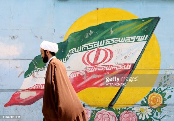 An Iranian cleric walks past a mural painting of the national flag in the capital Tehran on August 27 2019 Iranian President Hassan Rouhani today...
