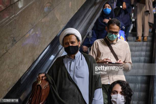 An Iranian cleric wearing a protective face mask to prevent himself of infection by the new coronavirus disease , in an underground station in...