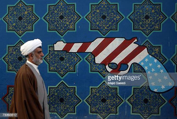 An Iranian clerric walks past a mural on the wall of the former U.S. Embassy, apparently undaunted by media reports of potential airstrikes by the US...