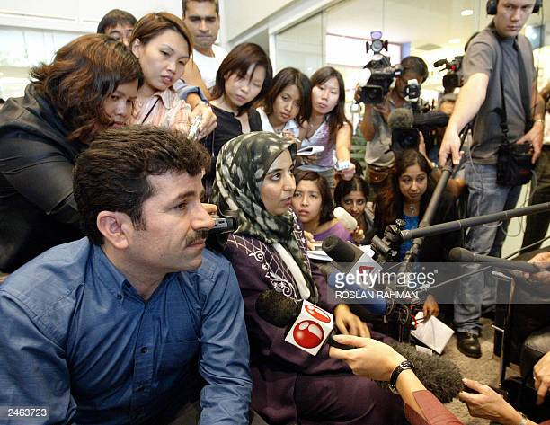 An Iranian couple are surrounded by reporters at the lobby of the Raffles Hospital while waiting for updates on the twin sisters laden and Laleh...