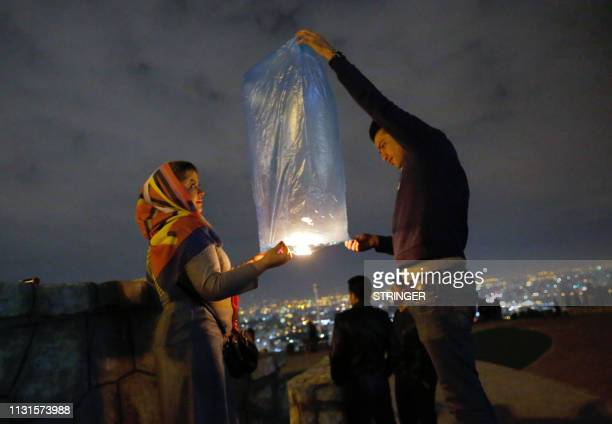 TOPSHOT An Iranian couple lights a lantern in a park in Tehran on March 19 2018 during the Wednesday Fire feast or Chaharshanbeh Soori held annually...