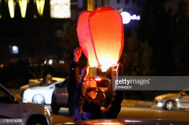 An Iranian couple lights a lantern in a park in Tehran on March 19 2018 during the Wednesday Fire feast, or Chaharshanbeh Soori, held annually on the...