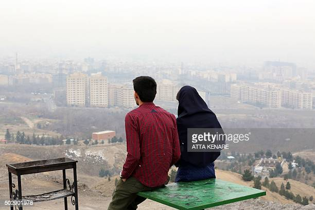 An Iranian couple look at a heavily polluted skyline as seen from western Tehran on December 30 2015 Exhaust fumes from the five million cars and...
