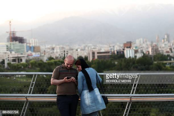 An Iranian couple look at pictures on their smartphone on the Nature bridge in the capital Tehran on May 18 on the eve of the presidential elections...