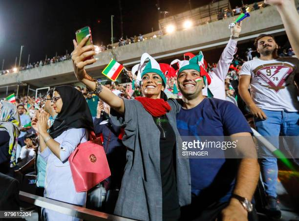 An Iranian couple pose for a 'selfie' photograph with a cell phone while cheering for their national fooball team during a screening of the Russia...