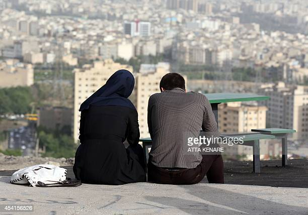 An Iranian couple sit together in the northwestern Shahran neighbourhood overlooking Tehran on June 7 2014 One in three marriages fails in the...
