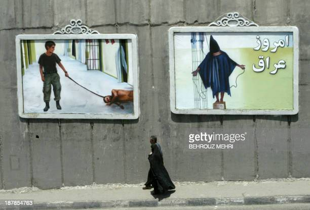 An Iranian couple walk past mural paintings depicting scenes from the torture of Iraqi prisoners by US soldiers at the Abu Ghraib prison near...