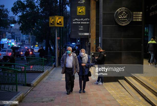 An Iranian couple wearing protective face masks walk past an underground station in northern Tehran at sunset on day-3 of two-week total lockdown on...