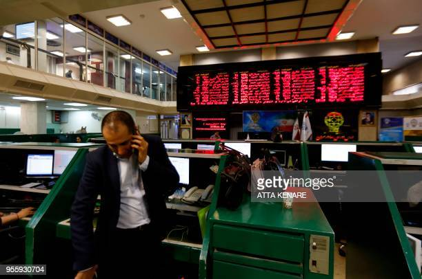 An Iranian dealer monitors the stock market at the stock exchange in the capital Tehran on May 8 2018 Renewed nuclear sanctions would certainly cause...