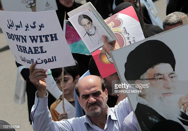 An Iranian demonstrator holds an antiIsrael placard and a portrait of the Islamic republic's late founder Ayatollah Ruhollah Khomeini while another...