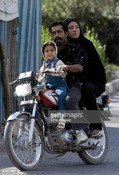 An Iranian family is seen on a motorbike 05 November 2004 in the southeastern devastated city of Bam where a powerful earthquake killed more than...