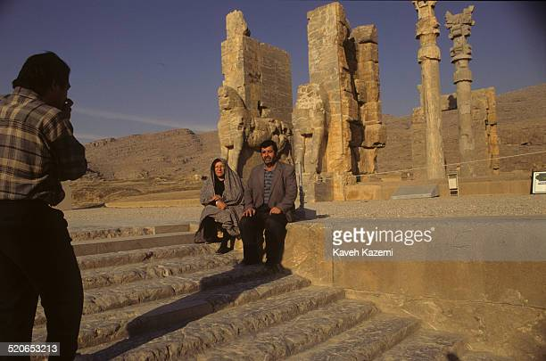 An Iranian family make a souvenir photo while sat on the staircase in the ruins of Persepolis or Takht-e Jamshid near Shiraz, Iran.