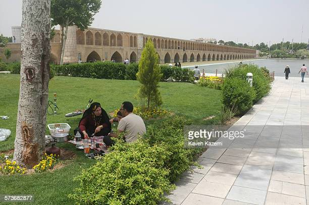 An Iranian family picnics while sat on a mat on the grass near Sio Se Pol Bridge on 11th May 2012 in Isfahan, Iran. The water in Zayande river...