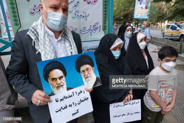An Iranian family stands outside a polling station in downtown Tehran holding portraits of Iran's Supreme Leader Ayatollah Ali Khamenei and late...