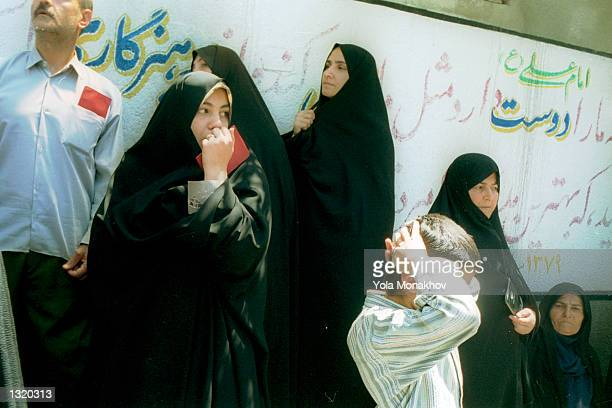An Iranian family takes out their passports as they queue up to vote in the presidential election June 8, 2001 in northern Tehran, Iran. President...