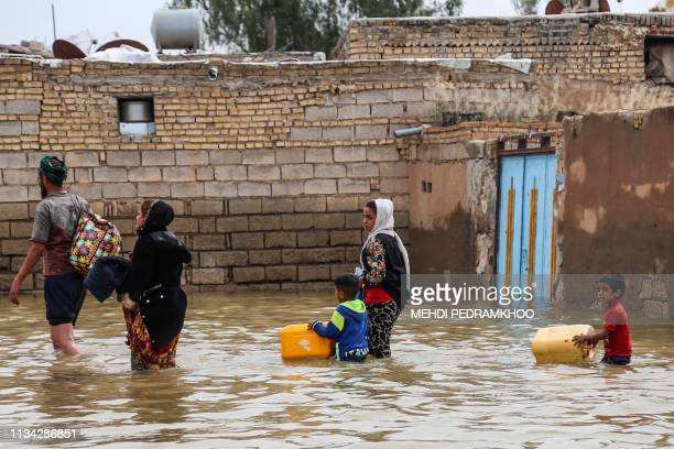 An Iranian family walks through a flooded street in a village around the city of Ahvaz in Iran's Khuzestan province on March 31 2019 Iranian...