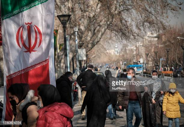 An Iranian family wearing protective face masks walk along a street-side near Tehrans Traditional Grand bazaar amid the COVID-19 outbreak in Iran on...