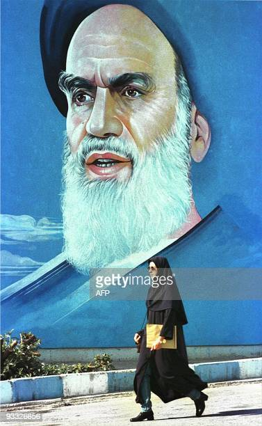 An Iranian female student passes by a mural of Iran's Islamic revolution founder the late Ayatollah Ruhollah Khomeini 03 February in Tehran Iran...