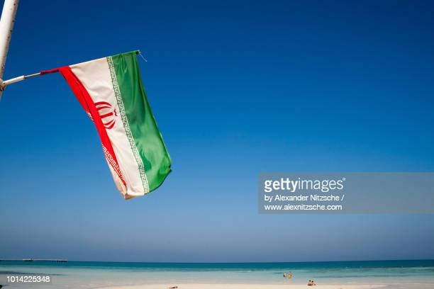 an iranian flag at the beach of kish island, iran - iranian flag stock photos and pictures