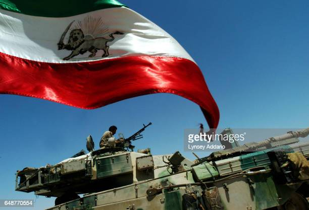 An Iranian flag flies above male soldiers with the Mujahedeen Khalq Organization MKO as they service tanks on their main base at Camp Ashraf near...