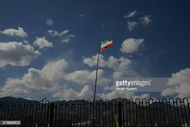 An Iranian flag seen amass against the cloudy blue sky on April 22 2013 in Tehran Iran