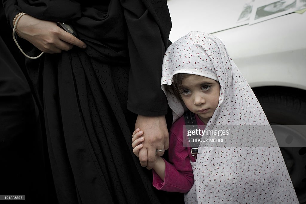 An Iranian girl holding her mother's hand attends the funeral of Iranian armed forces who were killed during the Iran-Iraq war (1980-88) after the Friday prayers in Tehran on May 14, 2010. Iran held a funeral for 89 soldiers who were discovered by a searching team on the Iran-Iraq border.