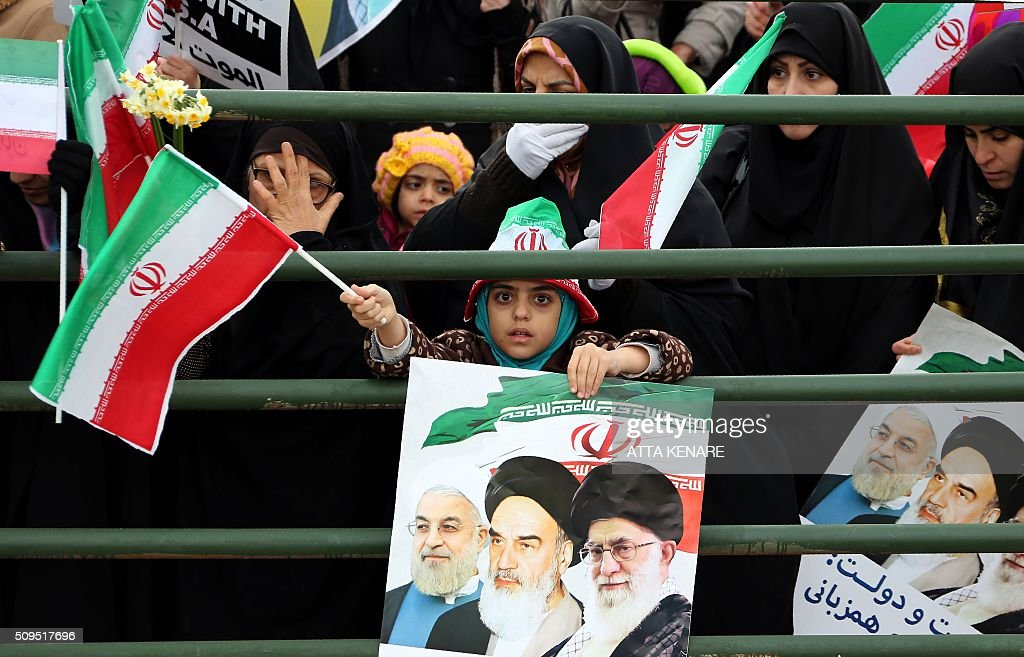 An Iranian girl holds a poster with a portrait of President Hassan Rouhani (L), Iran's late leader Ayatollah Ruhollah Khomeini and Iran's Supreme Leader Ayatollah Ali Khamenei during celebrations in Tehran's Azadi Square (Freedom Square) to mark the 37th anniversary of the Islamic revolution on February 11, 2016. Iranians waved 'Death to America' banners and took selfies with a ballistic missile as they marked 37 years since the Islamic revolution, weeks after Iran finalised a nuclear deal with world powers. KENARE