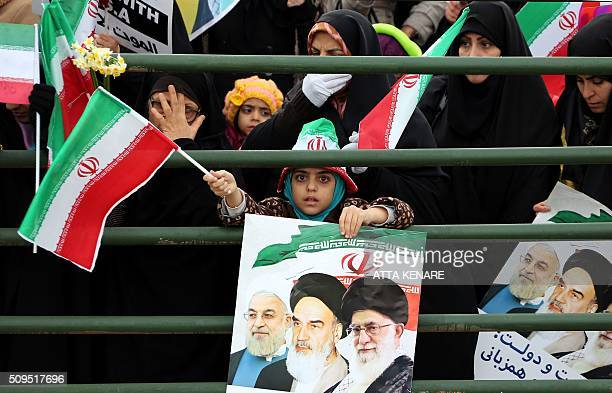 An Iranian girl holds a poster with a portrait of President Hassan Rouhani Iran's late leader Ayatollah Ruhollah Khomeini and Iran's Supreme Leader...