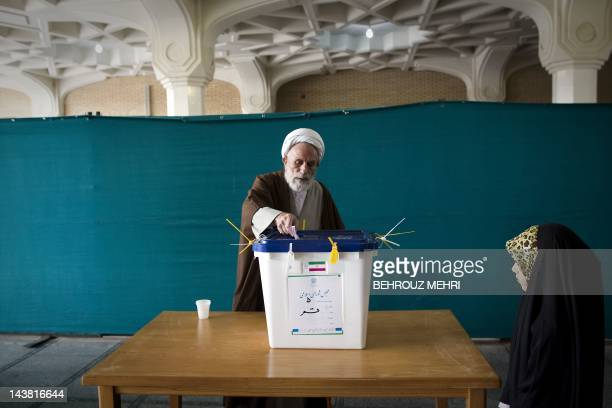 An Iranian girl looks at a clergyman casting his ballot at a polling station at the Massoumeh shrine in the religious city of Qom 130 kms south of...