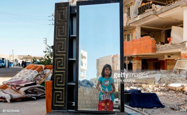 TOPSHOT An Iranian girl looks through a salvaged mirror from a damaged building in the town of Sarpole Zahab in the western Kermanshah province near...