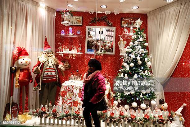 An Iranian girl poses for a picture in front of Christmas decorations outside a shop in the capital Tehran on December 24 on Christmas eve / AFP /...