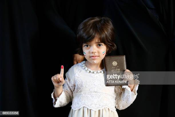 TOPSHOT An Iranian girl shows her inkstained finger and her mother's ID after the latter voted for the presidential elections at a polling station in...