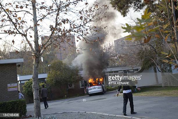 An Iranian hardline protester is seen inside the British Embassy as a diplomatic vehicle is set on fire by demonstrators who stormed the mission in...